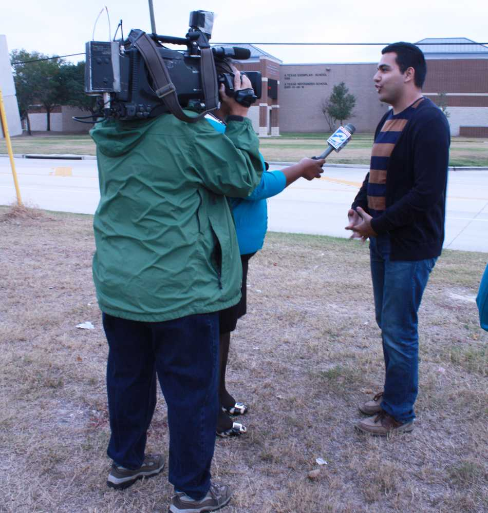 LIghts,  camera, action: A news reporter asks senior Victor Garibaldi about the gun incidents. Garibaldi said he thought Cy Creek was a safe campus. photo by Kristin Russell.