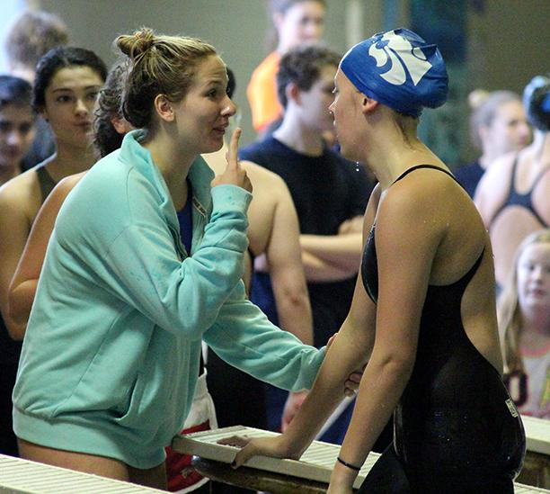 Senior Annie Eubanks congratulates Sophomore Tara Howard on her swim in the 200m medley relay.
