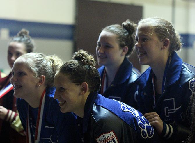 Senior Tori Karker, freshman Sydney Coachman and sophomores Tara Howard and Brandi Courtney pose for pictures on the podium after placing second in the 200m medley relay.