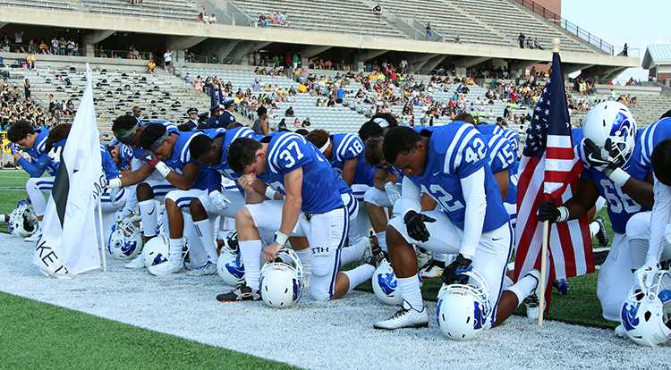 Cy Creek Cougars take a kneel during the National Anthem