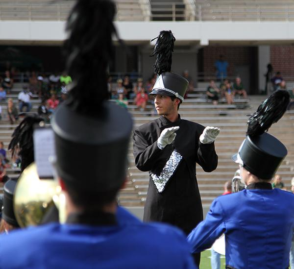 Senior Andres Bryan directs the band during the  halftime performance.