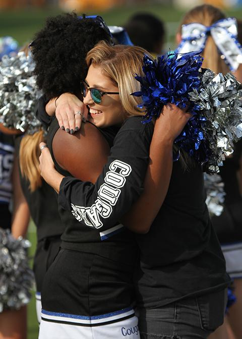 Cheerleaders hug at the conclusion of he last football game.
