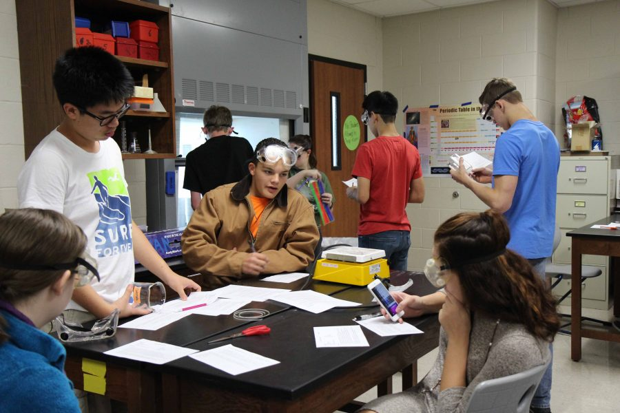 Chemistry students gather around to work on a lab