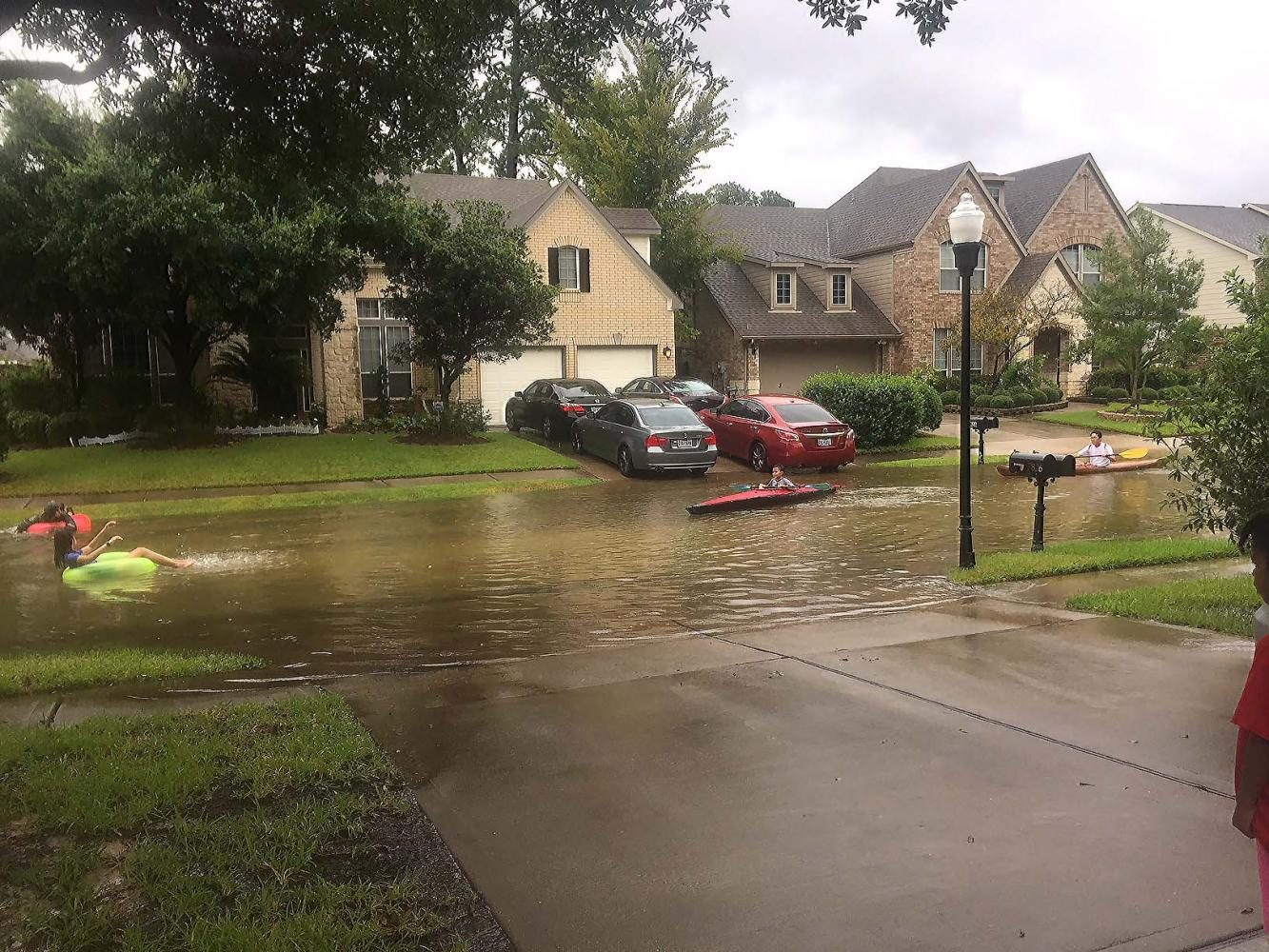 People in inner tubes and canoes float down a flooded street.