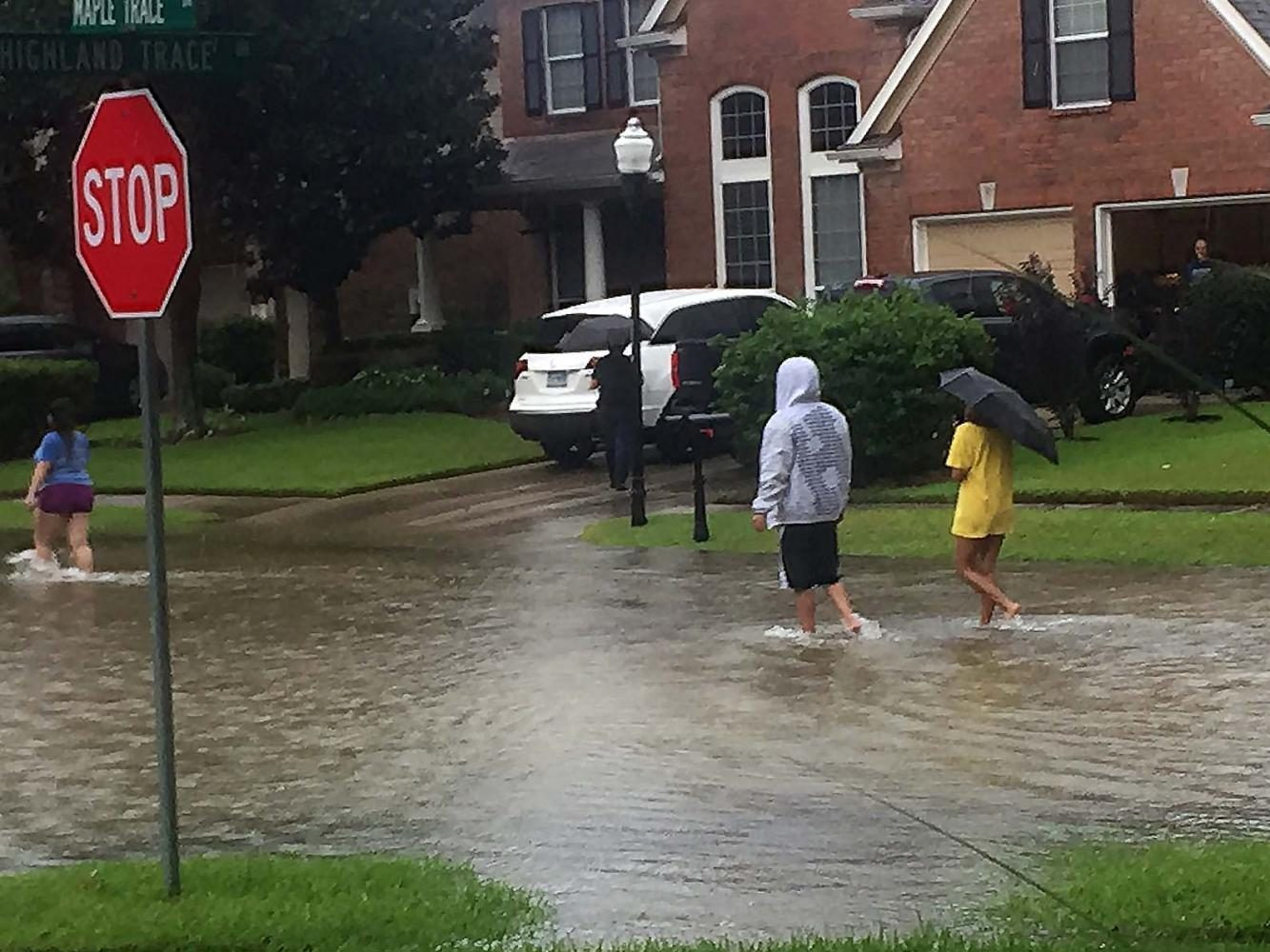 """People wade through the water in a flooded neighborhood. """"I felt so bad for the homeowners. Helping them out was probably the best thing I could do,"""" McClain said. """"I'm just glad they're alive."""""""