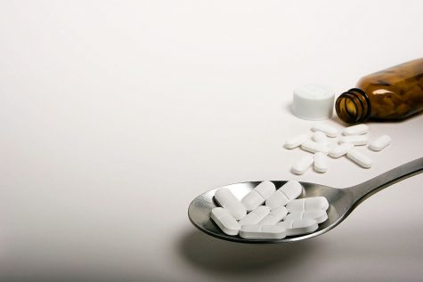 A bottle falls next to some pills in the background with a spoon in the foreground holding more pills.