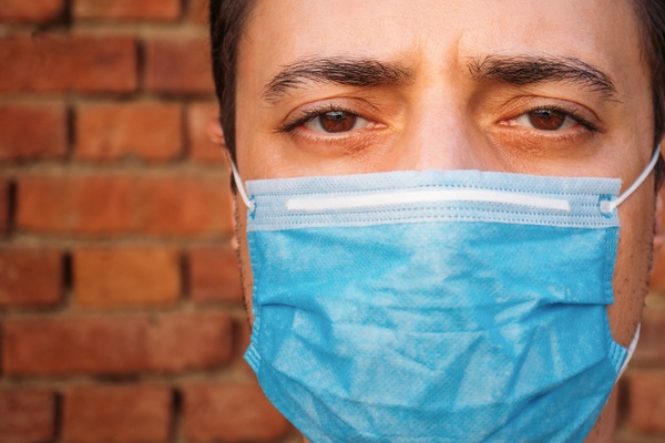 Close-up of a man with a medical face mask. Tight portrait shot with eye contact by Ivan Radic is licensed under CC BY 2.0